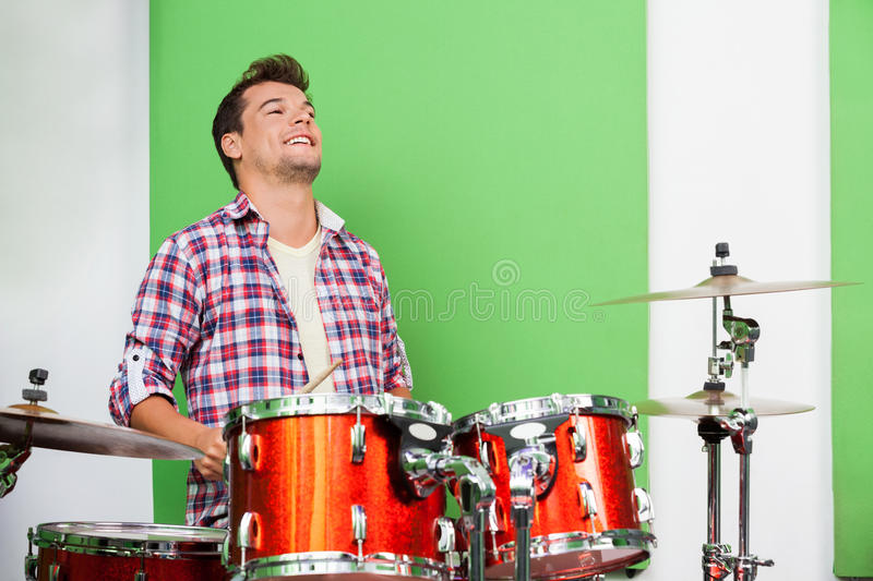Male Professional Playing Drums In Recording Studio stock photo
