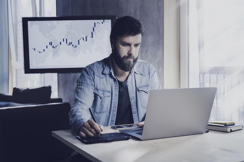 Male sitting at workplace and executing development projects using corporate software. Man working on laptop and tablet in office stock photography