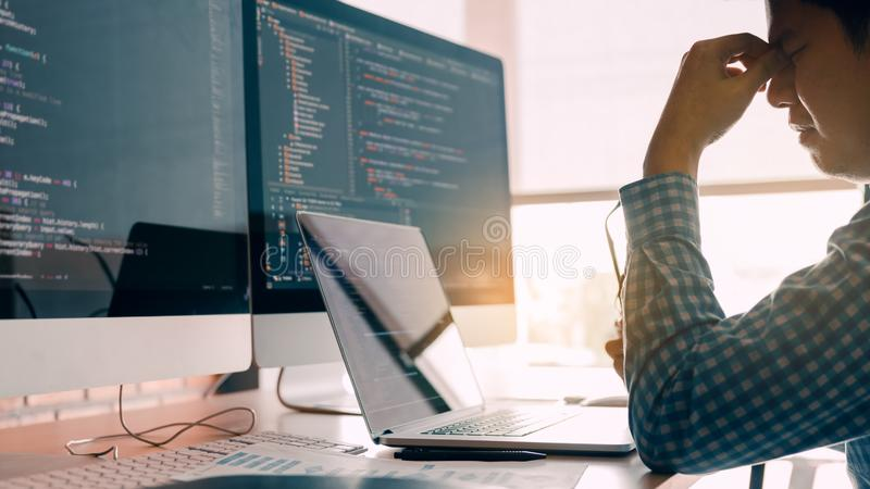 Male programmers are stressed at the office while working analyzing on desk in code at office room stock photos