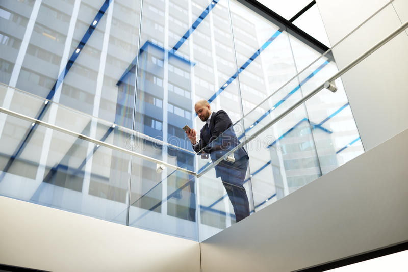 Male proud entrepreneur is chatting on mobile phone during work break. View from below of a man managing director is booking on-line via cell telephone place in royalty free stock photo