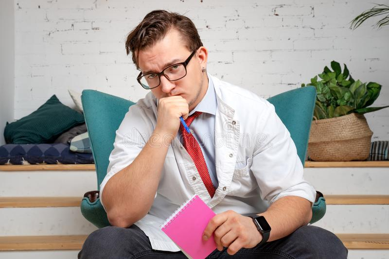 Male psychiatrist with pencil and clipboard sullenly looking into the camera, listening to the patient`s complaints royalty free stock photo