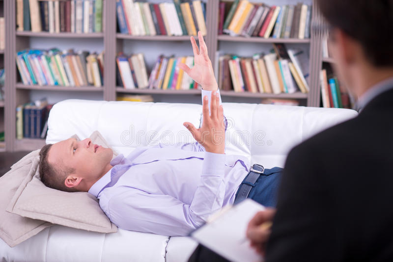Male psychologist noting down while patient is stock photo