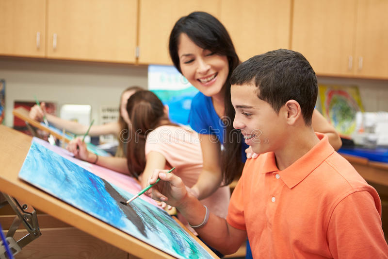 Male Pupil In High School Art Class With Teacher. Leaning Over Shoulder Smiling stock photography