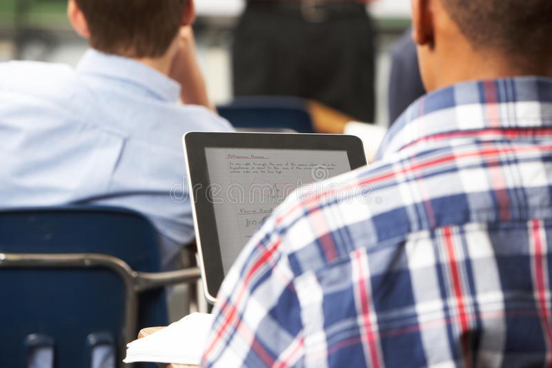 Male Pupil Using Digital Tablet In Classroom stock images