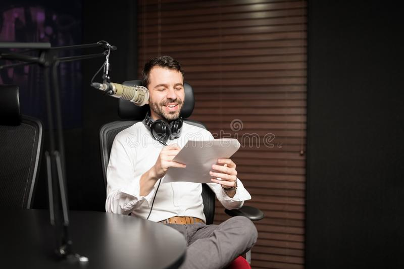 Male radio host broadcasting a show in studio. Happy young male radio host sitting at a table with headphones reading a script paper and broadcasting in a radio stock photo