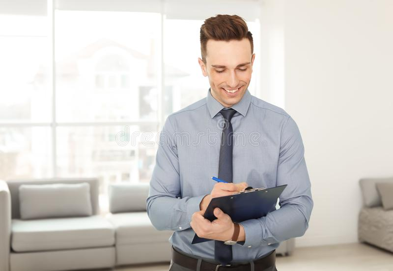 Male real estate agent with clipboard. Indoors royalty free stock photo