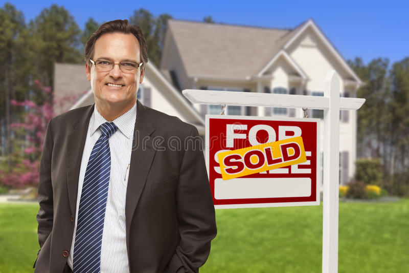 Male Real Estate Agent in Front of Sold Sign and House. Male Real Estate Agent in Front of Sold Home For Sale Sign and House stock image