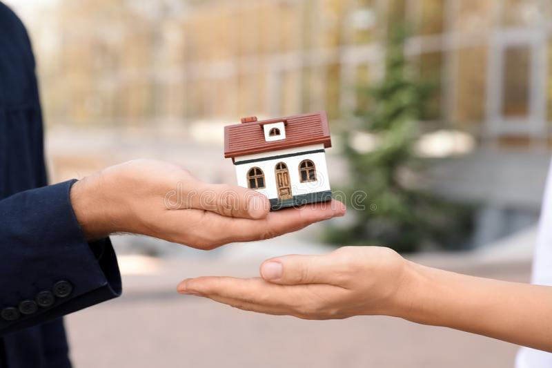 Male real estate agent giving house model to woman outdoors stock photo