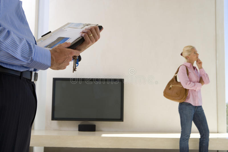 Male real estate agent and mature woman standing in living room, television in background. Male real estate agent and mature women standing in living room stock photo