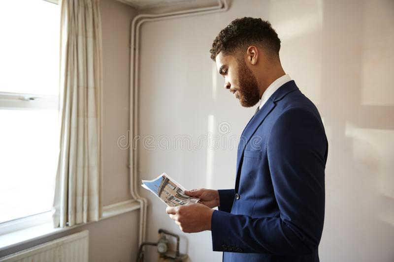 Male Realtor Looking At House Details In Property For Renovation royalty free stock photography