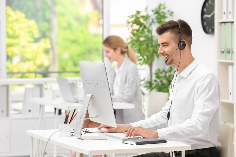 Male receptionist with headset at desk. In office royalty free stock photos