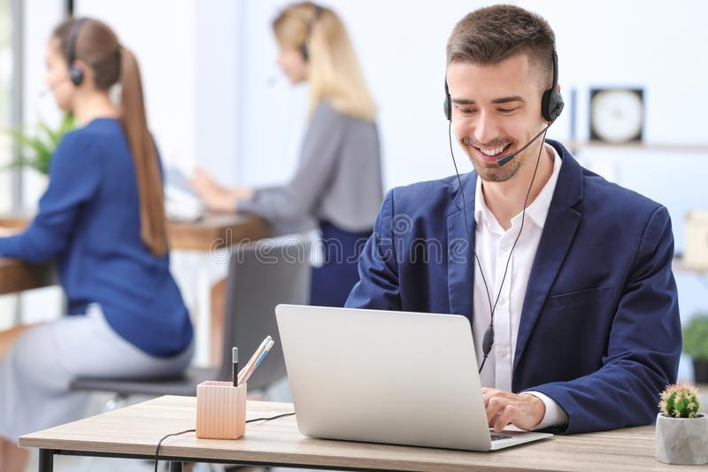Male receptionist with headset. At desk in office royalty free stock photo