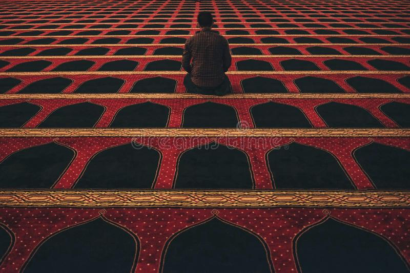 Male in red shirt kneeling on a red and black carpeted floor stock photography