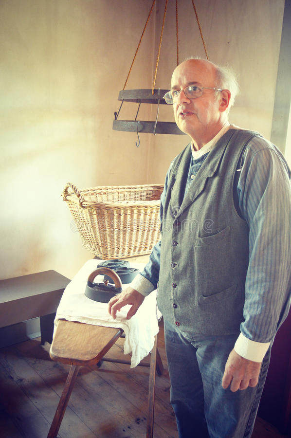 Man Ironing at Ironing Board stock images