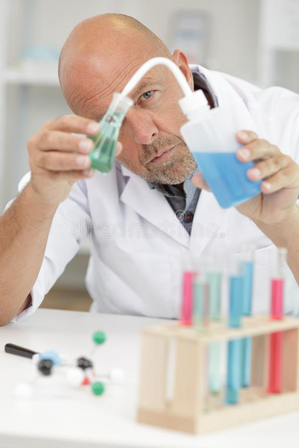 Male researcher holding flask with blue liquid in lab royalty free stock photography