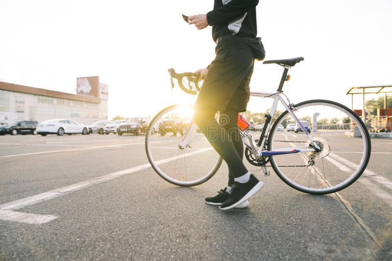 Male rider with a bicycle on the background of the sunset . Man cyclist rides a bike in the city royalty free stock image