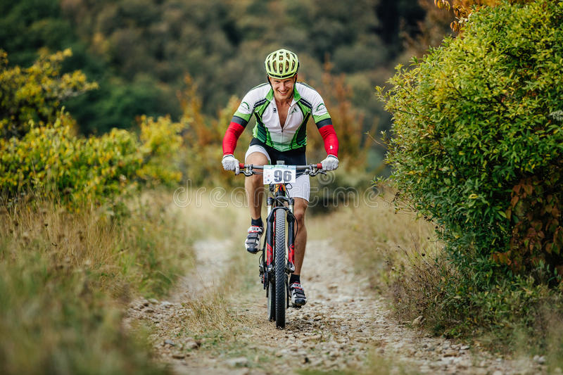 Male rider cyclist riding uphill on a mountain trail with smile on face royalty free stock image