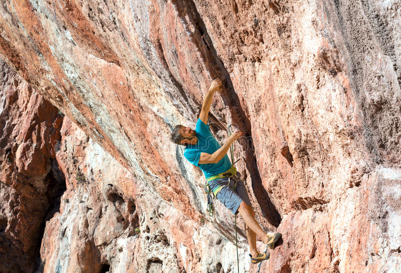 Male Rock Climber on high orange natural stone Wall royalty free stock image