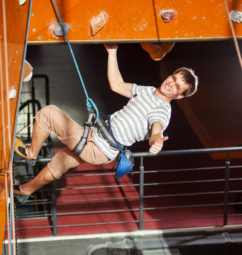 Male rock-climber practicing climbing on rock wall indoors. Athletic guy with special equipment and rope climbs on indoor wall, shows sign of class stock images