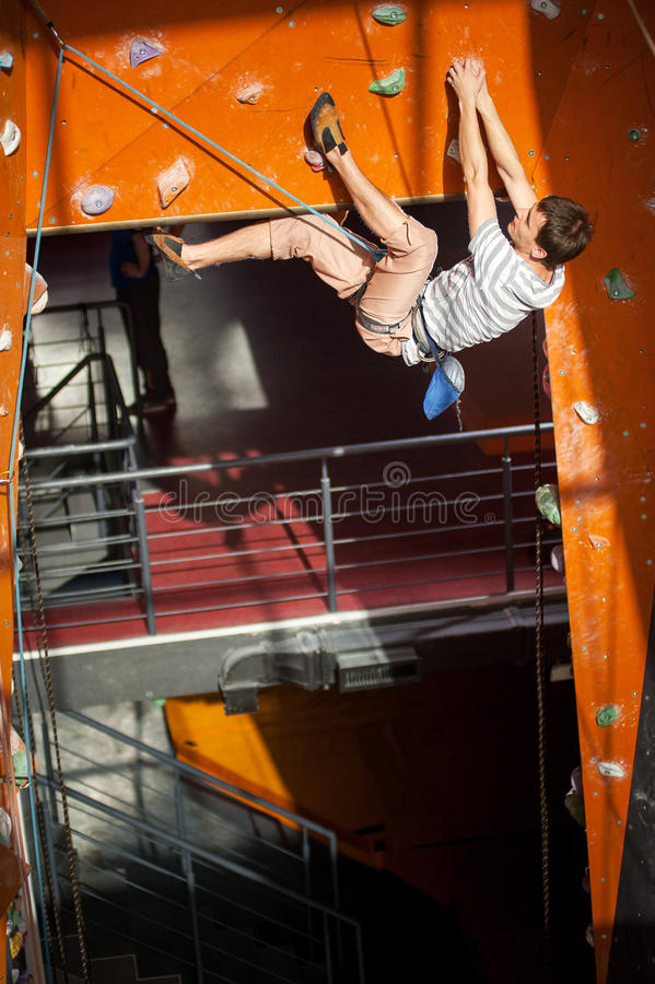Male rock-climber practicing climbing on rock wall indoors. Athletic young male climber with special equipment climbs on an indoor rock-climbing wall royalty free stock images
