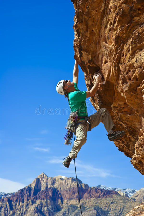 Male rock climber reaching for the summit. Male rock climber clings to an overhang in Red Rock Canyon on a sunny day