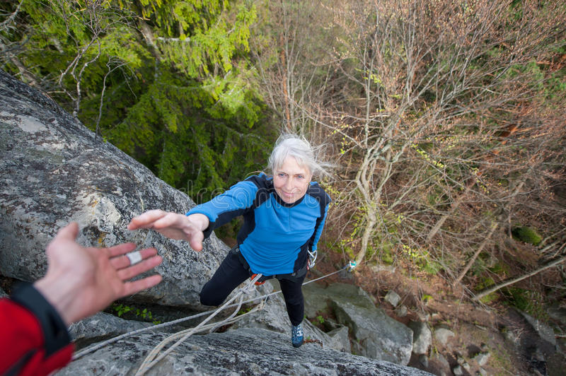 Male rockclimber is helping a climber female royalty free stock image