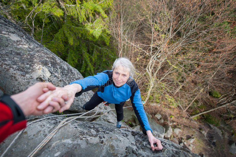 Male rockclimber is helping a climber female. To reach a peak of mountain. Man is belaying the woman stock photos
