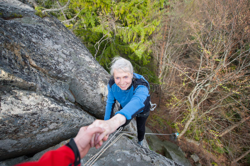 Male rockclimber is helping a climber female stock photo