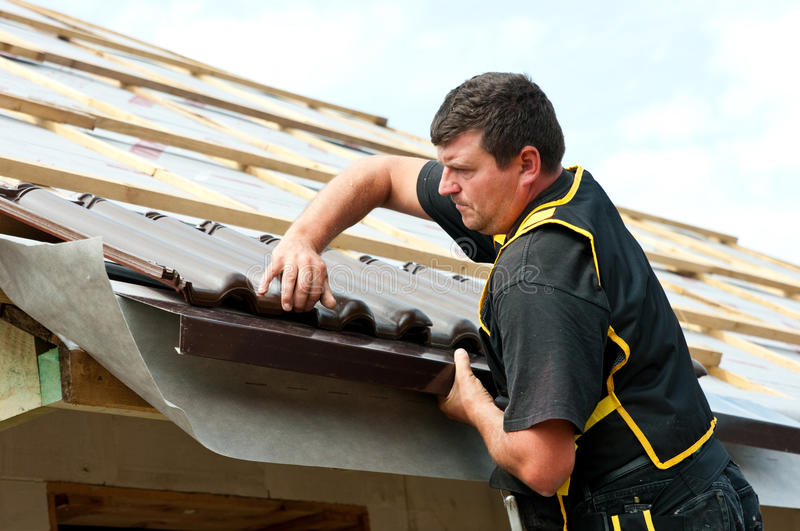 Male roofer fitting tiles. Half body portrait of middle aged roofer fitting or laying tiles on roof
