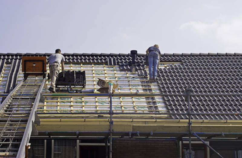 Male roofers fitting tiles royalty free stock photos