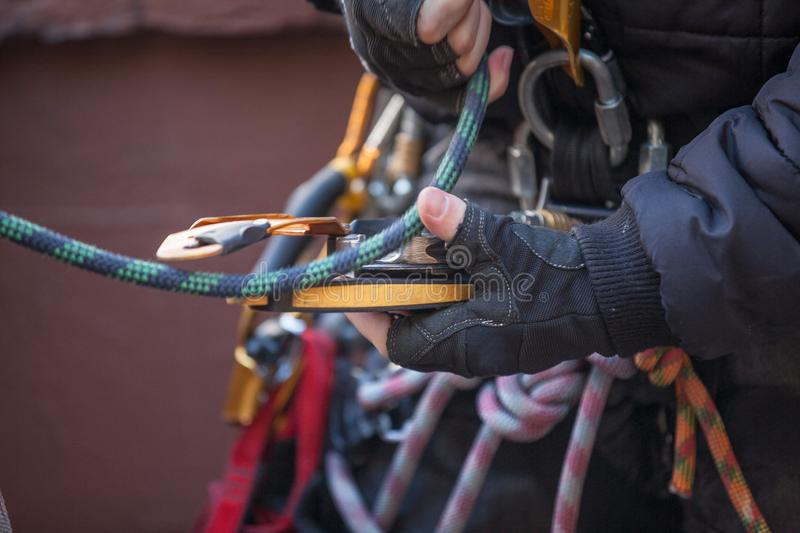 Male rope access worker dressing with industry fall protection yellow helmet abseiling safety body harness prior to work stock photography