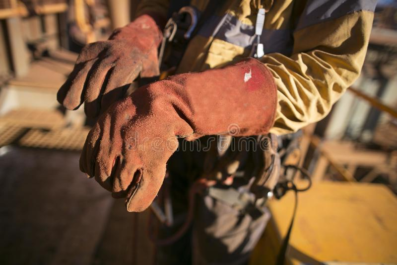 Construction worker wearing safety industry heavy duty reinforced quality leather gauntlet welding glove protection royalty free stock photography
