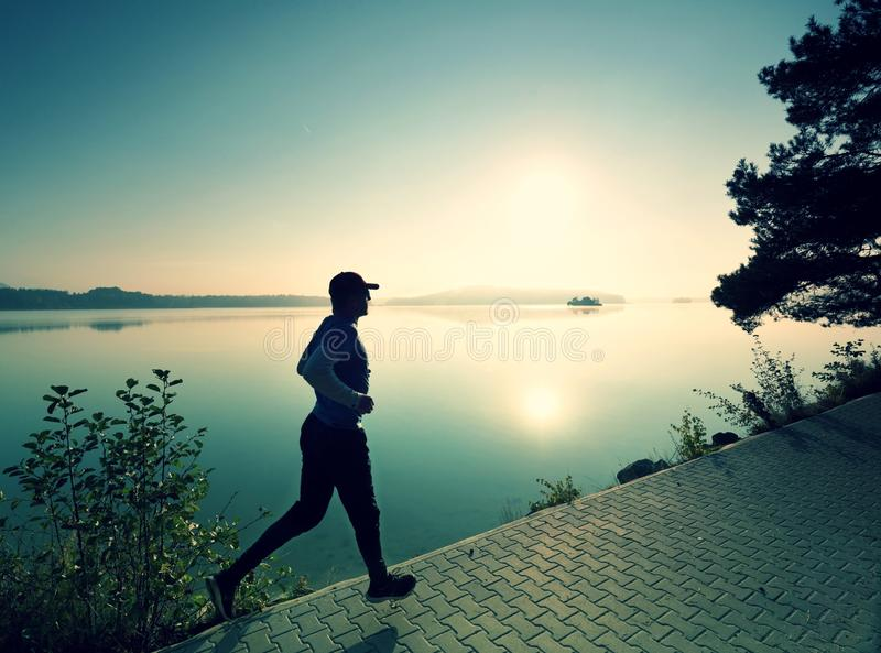 Male runner exercising on footpath at coast of island stock photos