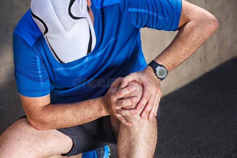 Male runner having problems in knee stock photography