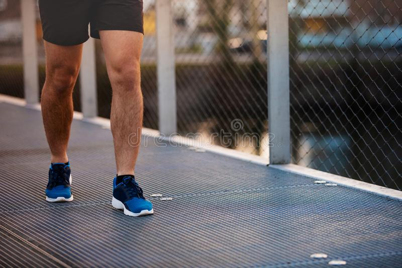 Male runner running in a city park over a bridge training. Young man sporty legs running outdoor along a bridge in the morning. Self overcome conquering royalty free stock photos