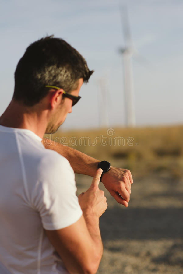 Male runner timing workout. Male motivated athlete using sport watch for timing running workout. Man training outdoor stock photography