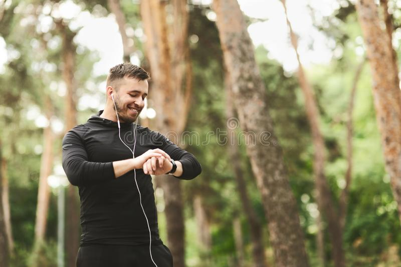 Male runner using smart watch to monitor his performance. stock photography