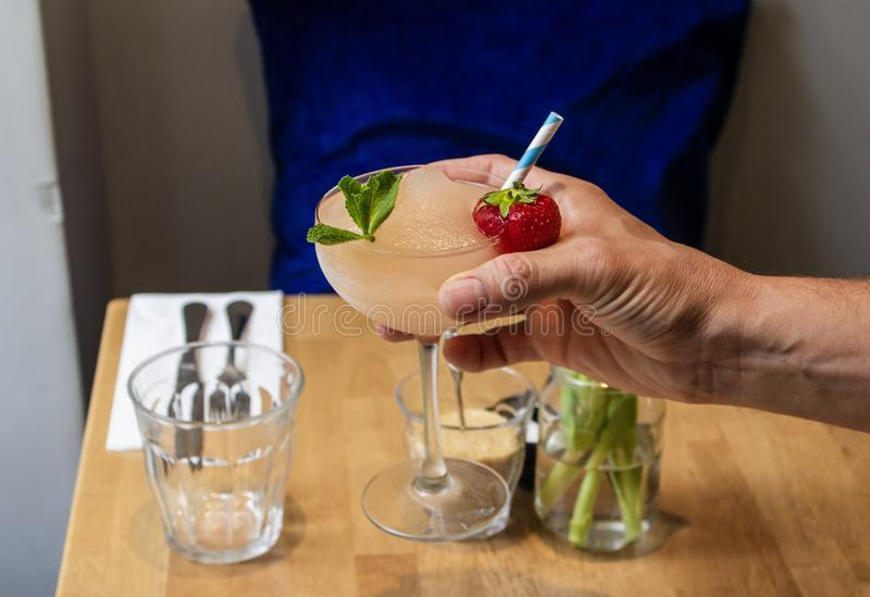Male`s hand holding a cocktail with strawberry and mint leaf with a blurred background stock image