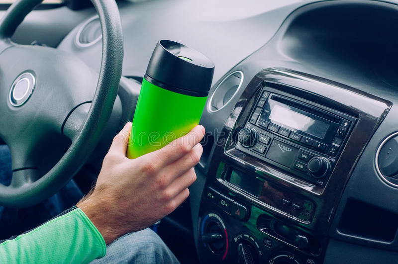 Male`s hand holding thermo mug. Close up of male`s hand holding thermo mug with hot coffee driving in a car royalty free stock images