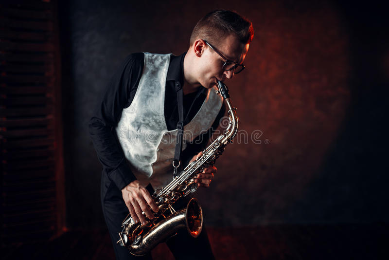 Male saxophonist playing jazz melody on saxophone. Professional male saxophonist playing jazz musical melody on saxophone royalty free stock image