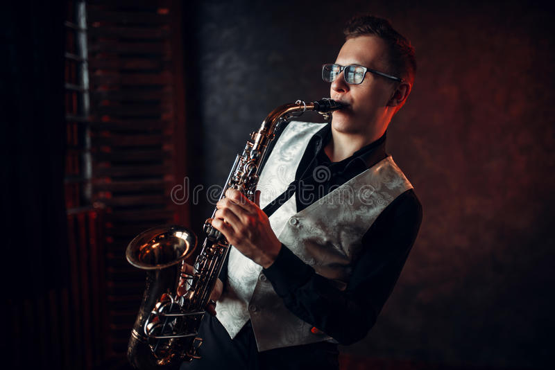 Male saxophonist playing jazz melody on saxophone. Professional male saxophonist playing jazz musical melody on saxophone stock photo