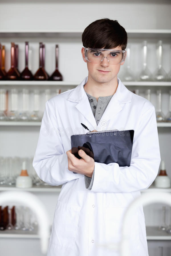 A Male Science Student Writing On A Clipboard Royalty Free Stock Photo