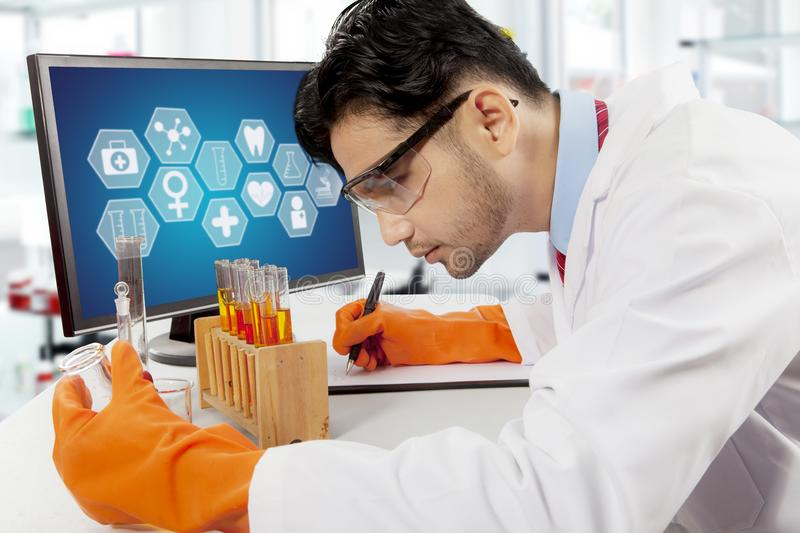 Male scientist doing chemical research. Male scientist doing science research in laboratory royalty free stock photos
