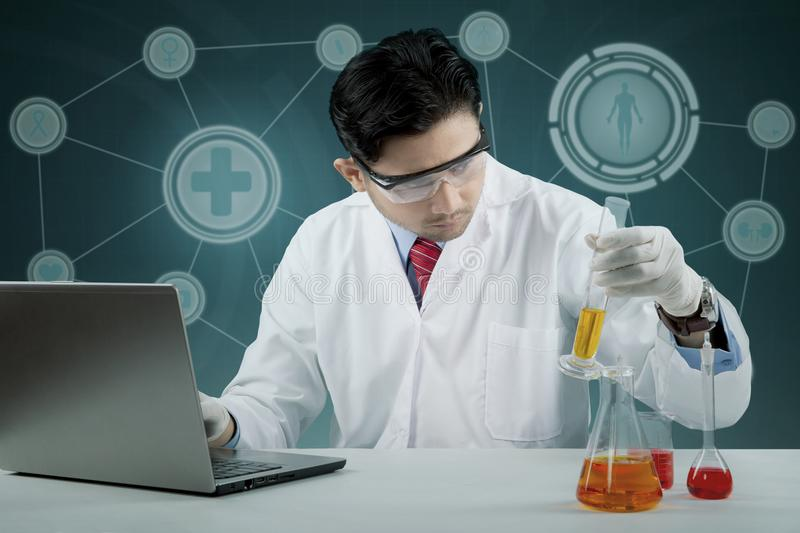 Male scientist doing chemical research. Male scientist doing science research in laboratory stock photos