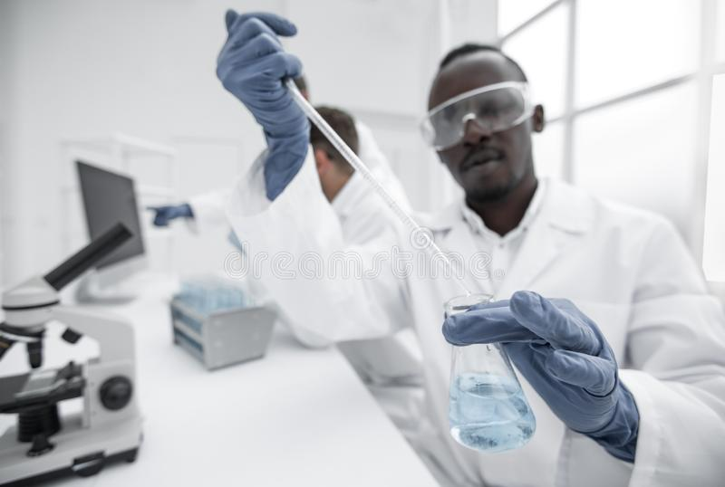 Male scientist with a flask makes a test in the laboratory. Young male scientist with a flask makes a test in the laboratory.science and health stock photography