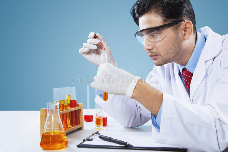 Male scientist makes chemical research. Portrait of male scientist makes chemical research by using chemical liquid in laboratory stock images