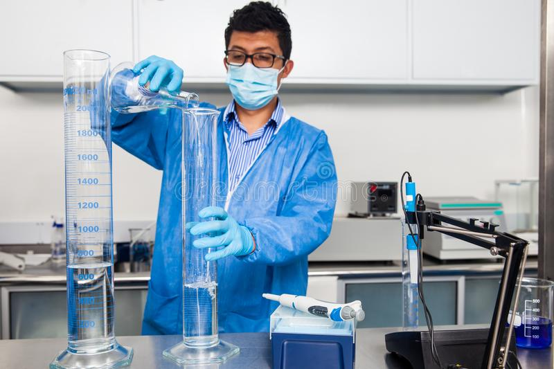 Male scientist working at laboratory dressed in blue stock images