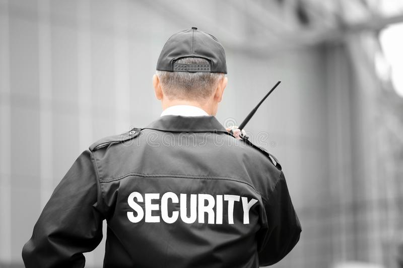 Male security guard using portable radio. Outdoors stock photos