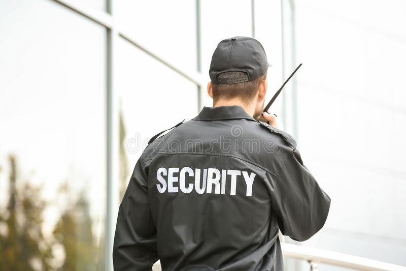 Male security guard using portable radio transmitter. Near building outdoors stock photography