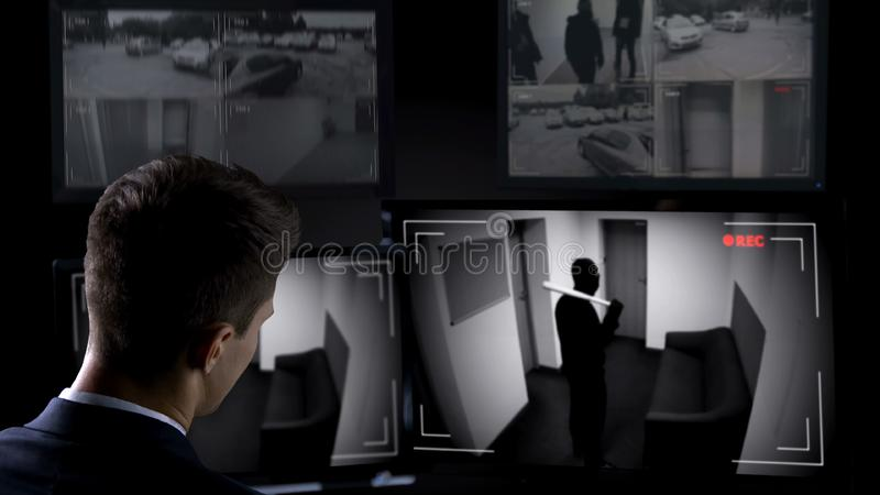 Male security guard watching bandit brake in building, CCTV footage, crime scene. Stock photo stock image
